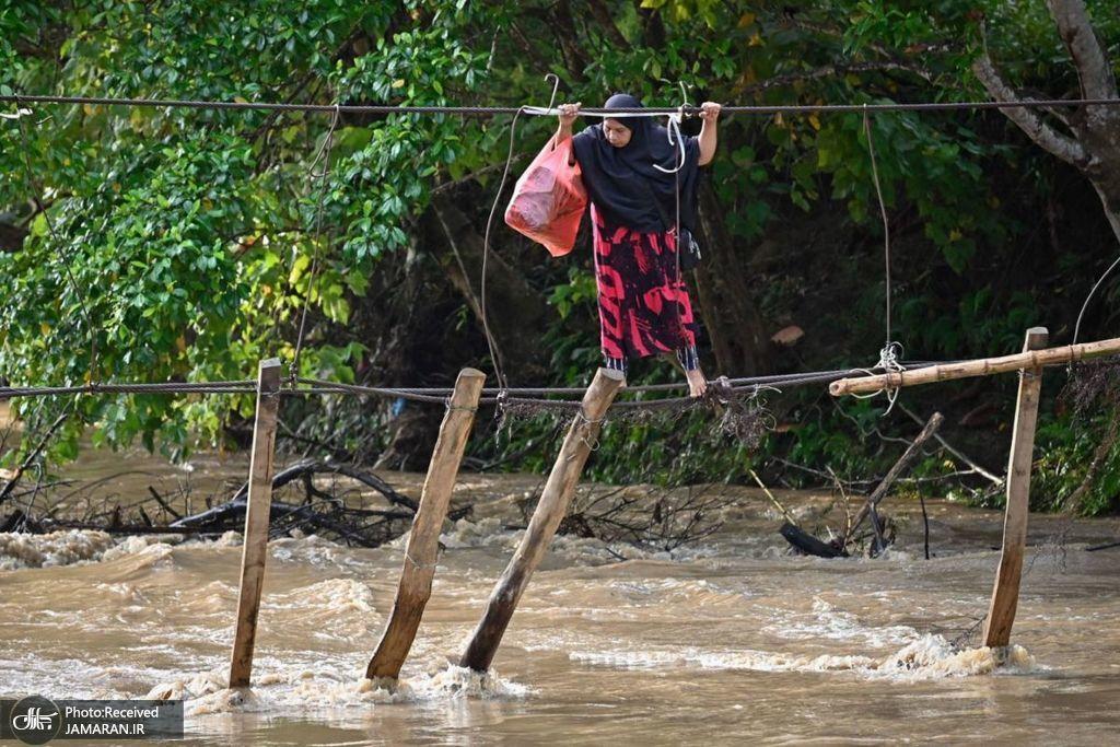 تصویر تکان دهنده از عبور سخت یک زن از رودخانه+عکس