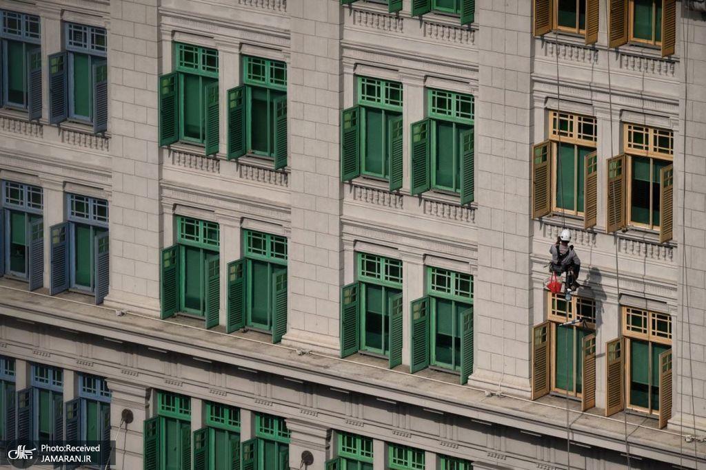 کارگری در حال تمیز کردن نمای ساختمان وزارت ارتباطات + عکس